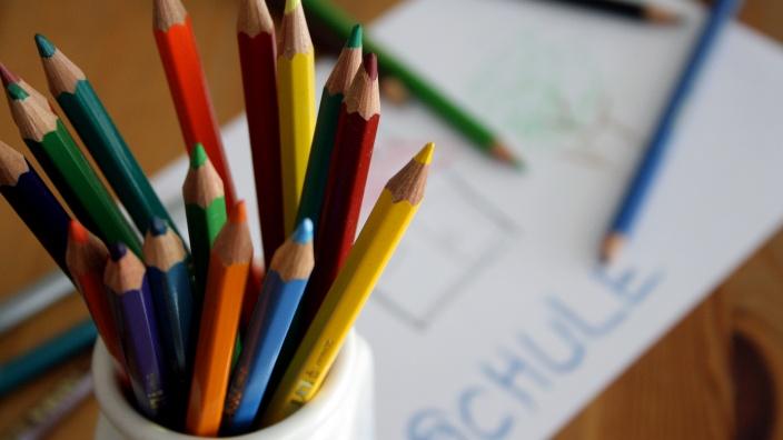 Stifte in einem Becher, ein Blatt Papier mit dem Wort Schule drauf